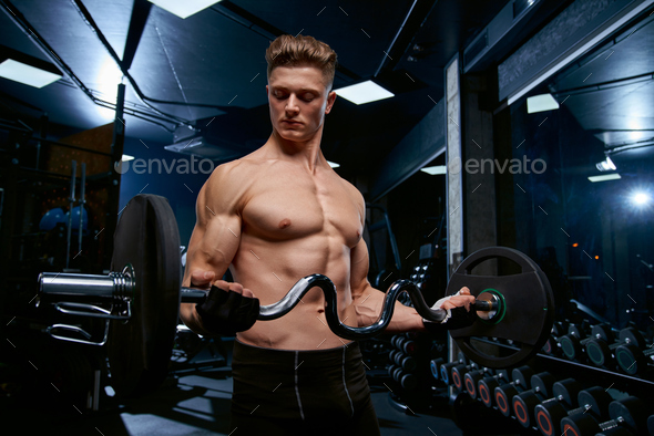 Shirtless sportsman training biceps with barbell - Stock Photo - Images