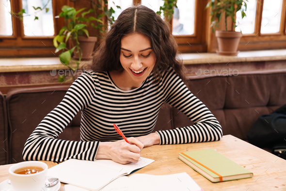 Image of student woman doing homework and smiling while drinking tea - Stock Photo - Images