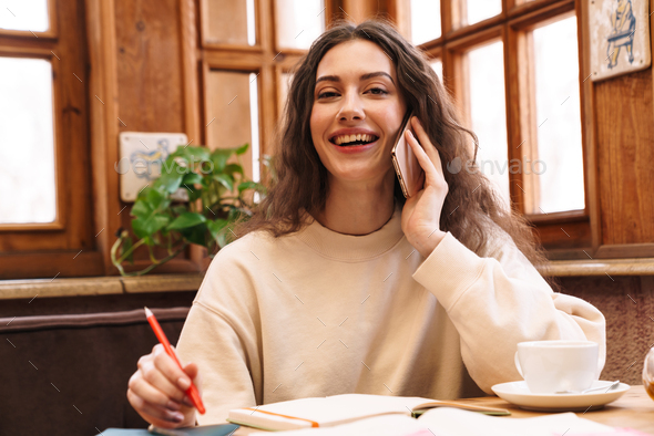 Image of woman doing homework and talking on cellphone in cafe - Stock Photo - Images
