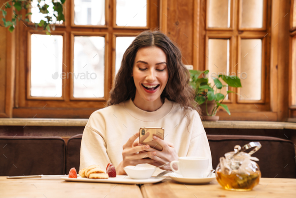 Image of woman drinking tea and using cellphone while sitting in cafe - Stock Photo - Images