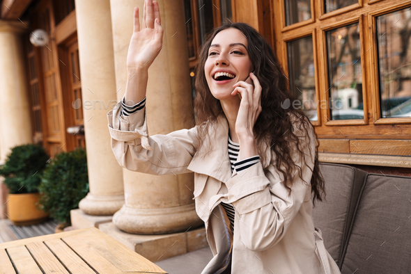 Image of smiling brunette woman talking on cellphone and waving hand - Stock Photo - Images