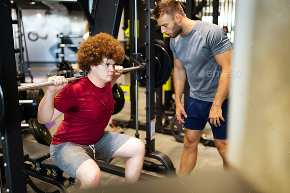Fat young men with trainer exercising at fitness gym - Stock Photo - Images