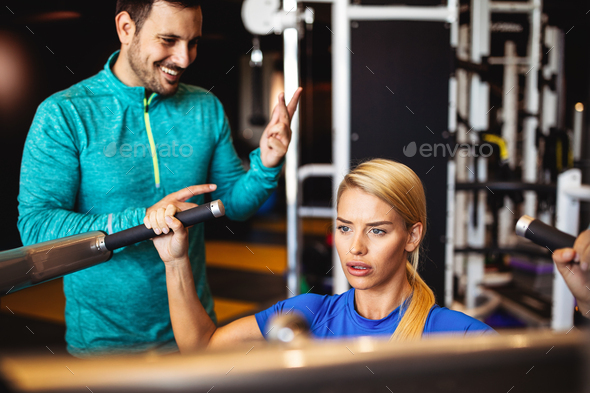 Woman with her personal fitness trainer in the gym exercising - Stock Photo - Images