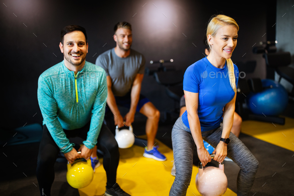 Young sporty people working out together with kettle bells in a gym - Stock Photo - Images