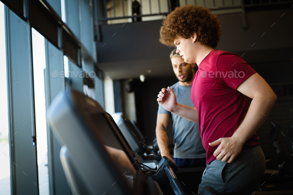Overweight young man exercising gym with personal trainer - Stock Photo - Images