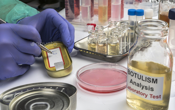 Experienced laboratory scientist writes on a canned food label - Stock Photo - Images