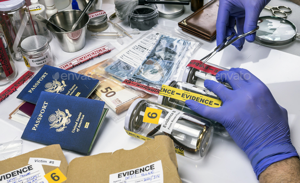 Scientific police opens with scissors a bag of evidence of a crime in scientific laboratory - Stock Photo - Images