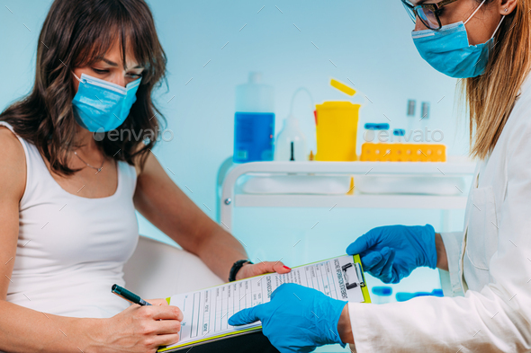 Female Patient Filling in Vaccine Information Statement. Corona Virus Vaccination. - Stock Photo - Images