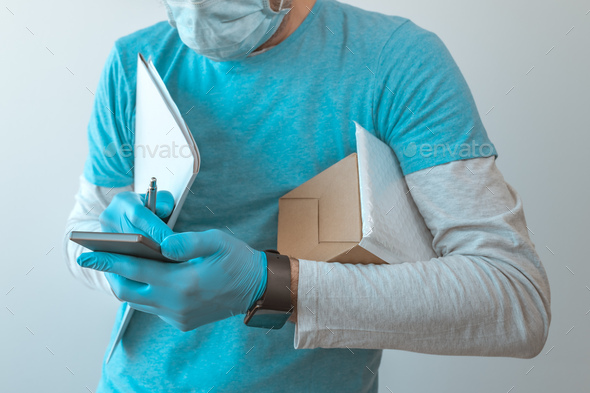 Delivery man with protective clothing using smartphone - Stock Photo - Images