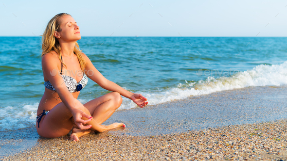 Woman in yoga pose sitting by sea - Stock Photo - Images