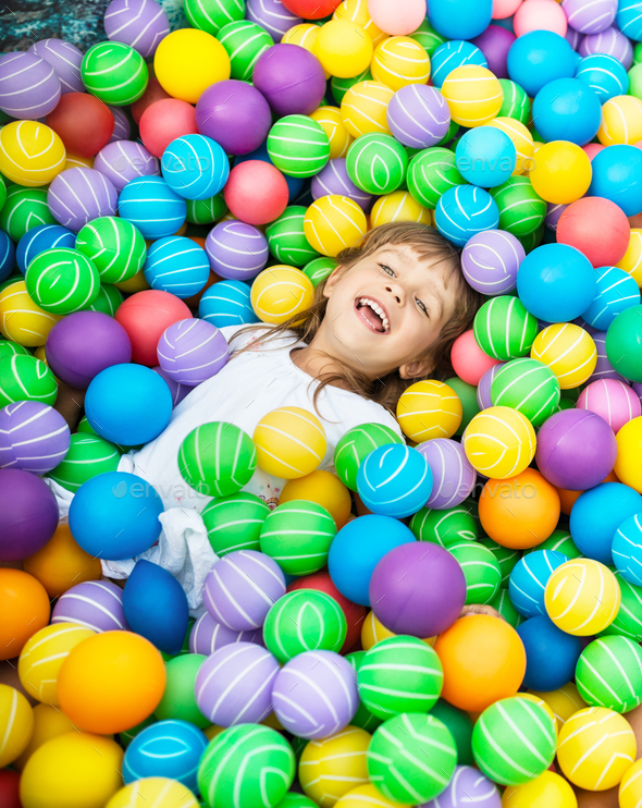 Child lying in pool with plastic balls - Stock Photo - Images