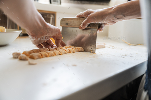 Low angle view of a woman cutting home made sweet potato gnocchi dough - Stock Photo - Images