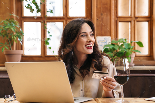 Image of adult woman holding credit card and working with laptop - Stock Photo - Images