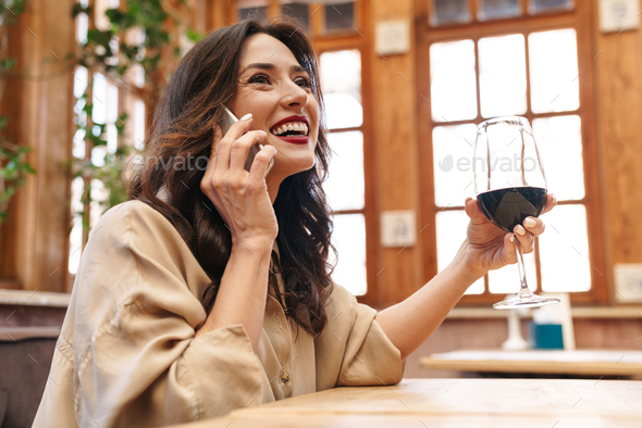 Image of adult woman drinking red wine and talking on mobile phone - Stock Photo - Images