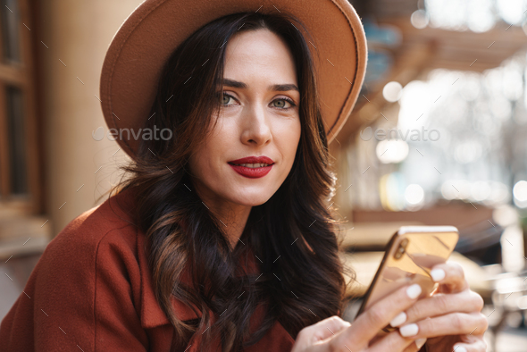 Image of pleased elegant adult woman in hat using mobile phone - Stock Photo - Images