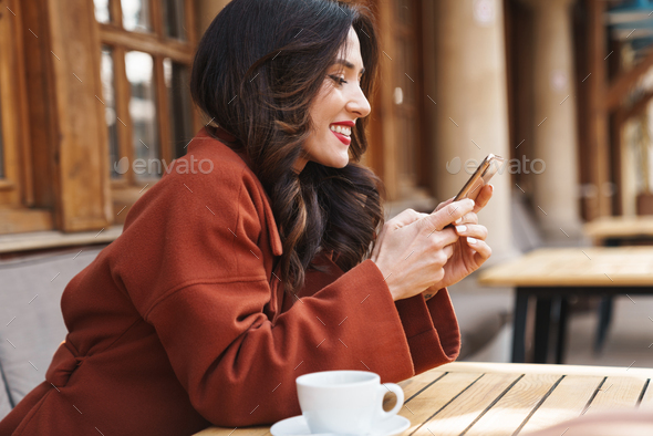 Image of happy adult woman using cellphone and drinking coffee - Stock Photo - Images