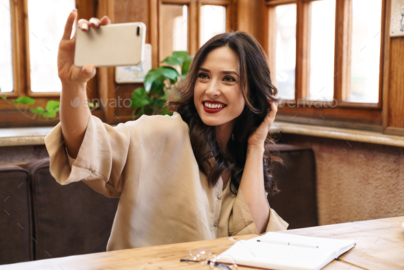 Image of cheerful adult woman smiling while taking selfie on cellphone - Stock Photo - Images