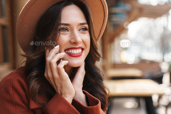 Image of joyful elegant adult woman smiling and talking on cellphone - Stock Photo - Images