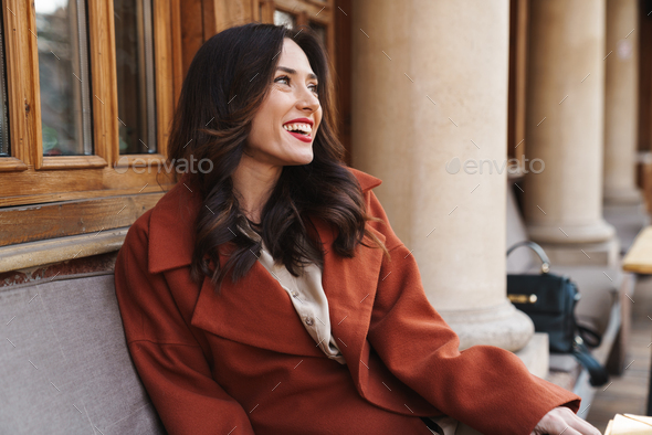 Image of happy adult woman laughing while sitting in street cafe - Stock Photo - Images