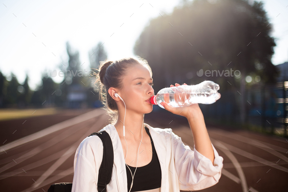 Portrait of beautiful girl in earphones drinking water on running track of stadium - Stock Photo - Images
