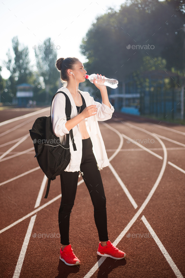 Girl in sporty top and legging with backpack on shoulder drinking pure water on racetrack of stadium - Stock Photo - Images