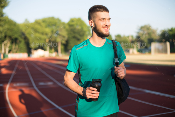 Young man with wireless earphones holding sport bottle happily looking aside on stadium - Stock Photo - Images