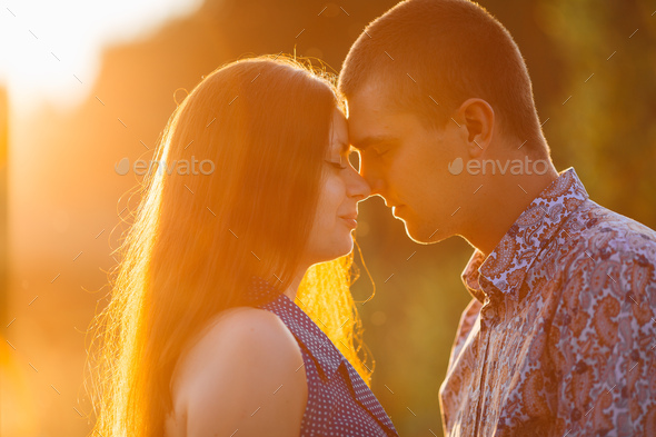 Portrait of brunette woman and man kissing and embracing face to face - Stock Photo - Images