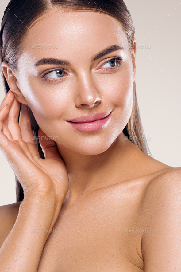Woman beauty healthy clean skin makeup young model hand touching face. Beige background. - Stock Photo - Images