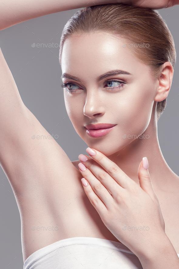 Armpit woman hand up deodorant care depilation concept. Gray background. Studio shot. - Stock Photo - Images