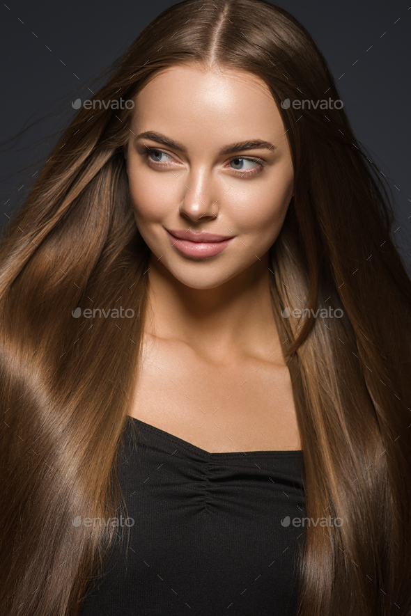 Brunette woman with long hair natural tanned skin. Dark background. - Stock Photo - Images