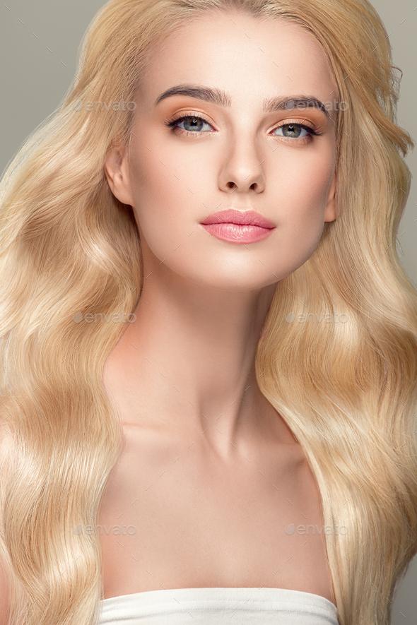 Blonde Hair Woman Beautiful Curly Hairstyle Wavy Long hair Natural Make up. Studio shot. On gray - Stock Photo - Images
