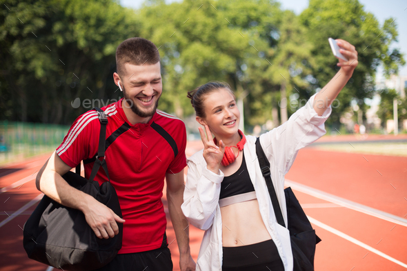 Young cheerful boy and beautiful girl happily taking selfie of cellphone happily on stadium - Stock Photo - Images