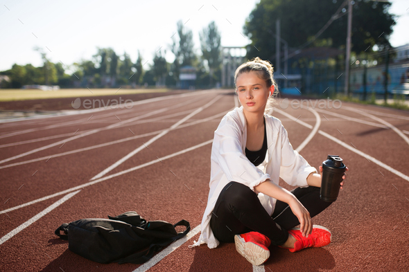 Beautiful girl with earphones holding bottle dreamily looking in camera on running track of stadium - Stock Photo - Images