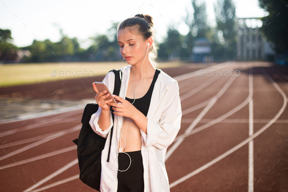Pretty girl in earphones with backpack thoughtfully using cellphone on treadmill of stadium - Stock Photo - Images