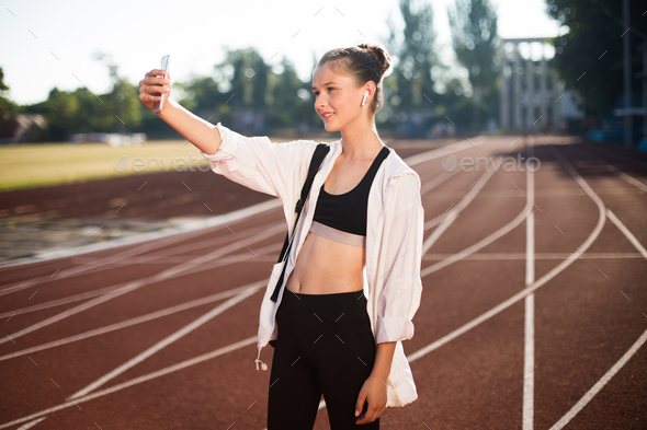 Beautiful smiling girl in earphones happily taking selfie on smartphone on treadmill of stadium - Stock Photo - Images