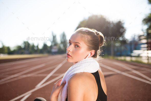Portrait of beautiful girl in earphones with towel on neck thoughtfully looking in camera on stadium - Stock Photo - Images