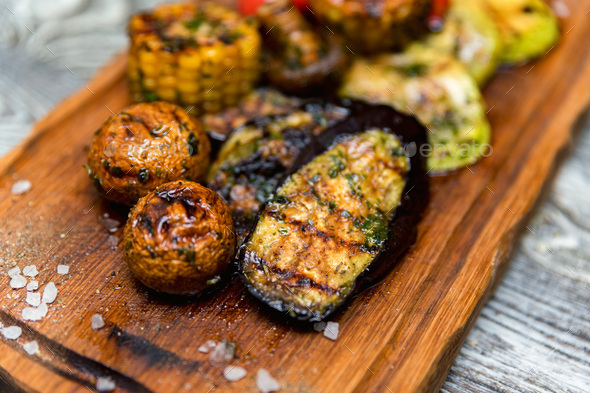 Various tasty grilled vegetables and mushrooms on rustic background - Stock Photo - Images