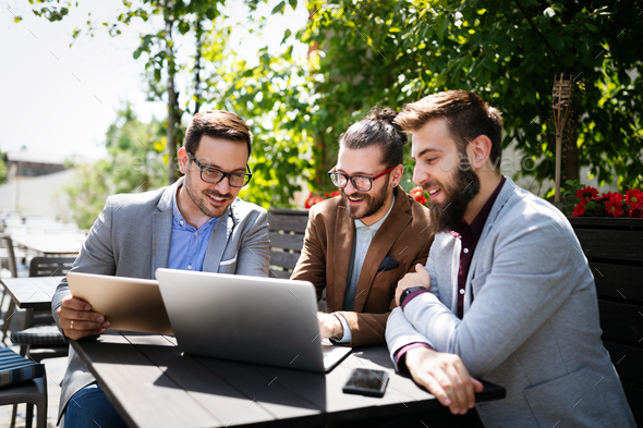 Cheerful happy businessmen using laptop at the meeting outdoor - Stock Photo - Images