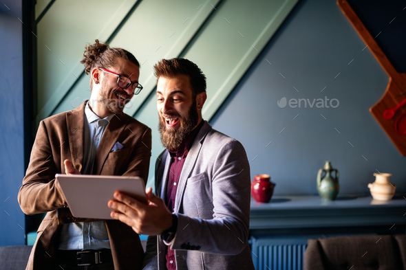Sharing fresh ideas. Group of young business people in smart casual wear talking and smiling - Stock Photo - Images