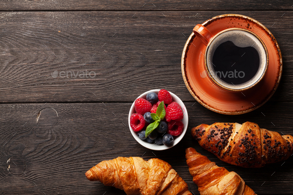 Coffee and croissants on wooden table - Stock Photo - Images