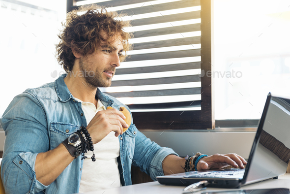 Young man using laptop while to have lunch. - Stock Photo - Images