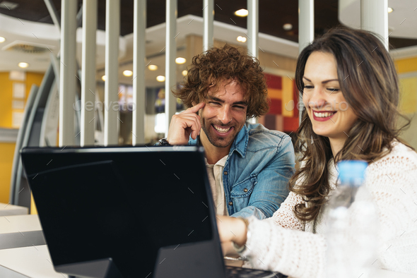 Couple using the laptop in the restaurant. - Stock Photo - Images