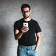 Man using his smartphone in front of a grey wall - PhotoDune Item for Sale