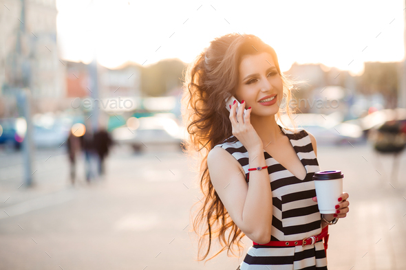 Beautiful brunette woman drinking coffee and talking to phone - Stock Photo - Images