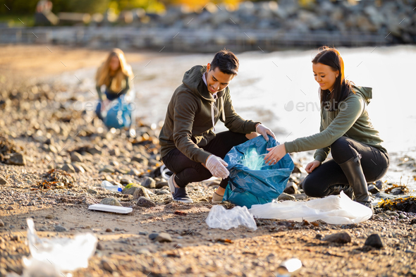 Team of dedicated and smiling volunteers collecting garbage at beach - Stock Photo - Images