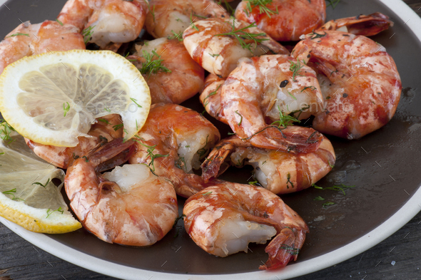 Baked shrimp with fresh tomato on a plate. Close up view. - Stock Photo - Images