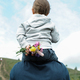 Little boy carried on his father's shoulders hiding wildflowers behind his back. - PhotoDune Item for Sale