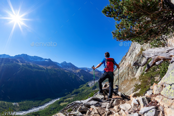 Hiker takes a rest observing a mountain panorama. - Stock Photo - Images