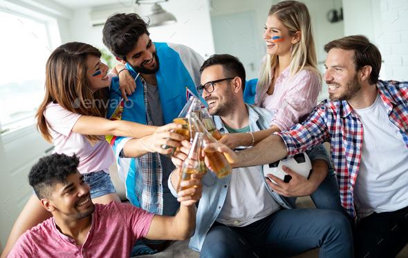 Group of friends sport fans watching soccer match toast