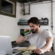 Bearded male drinking beer while searching for job - PhotoDune Item for Sale